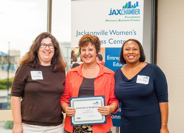 Marie is joined by mentor Donna Reade and emcee Julie Morgan as she receives her certificate of completion from the Marketing Matters program.